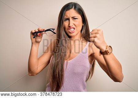 Young beautiful brunette optical woman holding vision glasses over isolated white background annoyed and frustrated shouting with anger, crazy and yelling with raised hand, anger concept