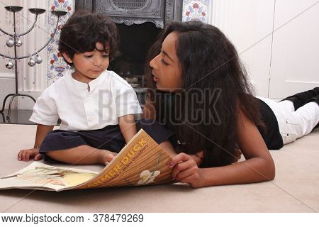 An Older Sibling Reads To Her Baby Brother, Taken In Witney, Oxfordshire In The Uk On The 27th Augus