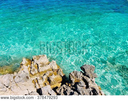 Rocks And Blue Cristal Sea Background. Summer Background