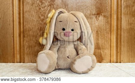 A Bunny Sits On A Wooden Background. Toy Rabbit.
