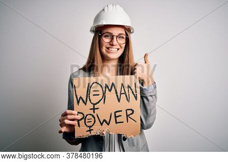 Young redhead architect asking for women rights holding banner with woman power message happy with big smile doing ok sign, thumb up with fingers, excellent sign