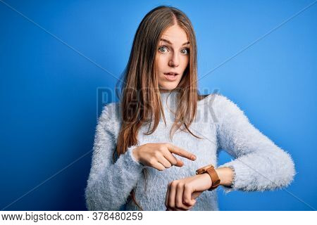 Young beautiful redhead woman wearing casual sweater over isolated blue background In hurry pointing to watch time, impatience, upset and angry for deadline delay