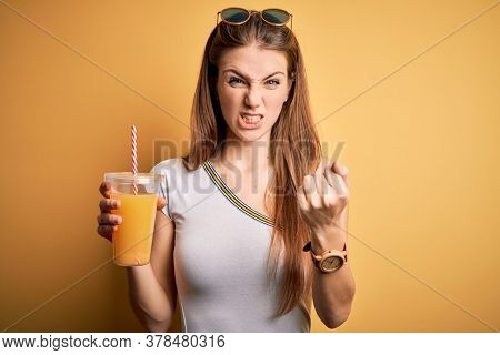 Young beautiful redhead woman drinking healthy orange juice over yellow background annoyed and frustrated shouting with anger, crazy and yelling with raised hand, anger concept
