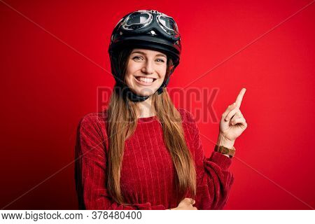 Young beautiful redhead motocyclist woman wearing moto helmet over red background with a big smile on face, pointing with hand and finger to the side looking at the camera.