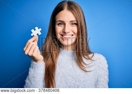 Young beautiful redhead woman holding piece of puzzle over isolated blue background with a happy face standing and smiling with a confident smile showing teeth