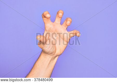 Hand of caucasian young man showing fingers over isolated purple background grasping aggressive and scary with fingers, violence and frustration