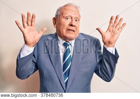 Senior handsome grey-haired businessman wearing elegant suit over white background clueless and confused with open arms, no idea and doubtful face.