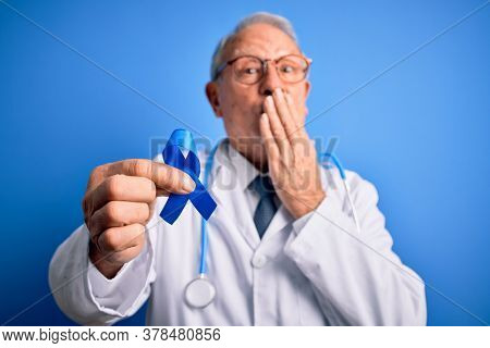 Grey haired senior doctor man holding colon cancer awareness blue ribbon over blue background cover mouth with hand shocked with shame for mistake, expression of fear, scared in silence.