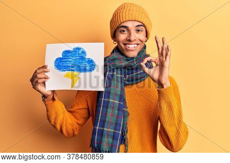 Young african amercian man holding thunder draw doing ok sign with fingers, smiling friendly gesturing excellent symbol
