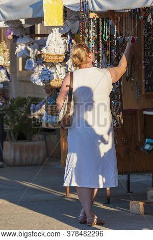 Woman In White Dress Standing On Market In Stari Grad On Hvar Island