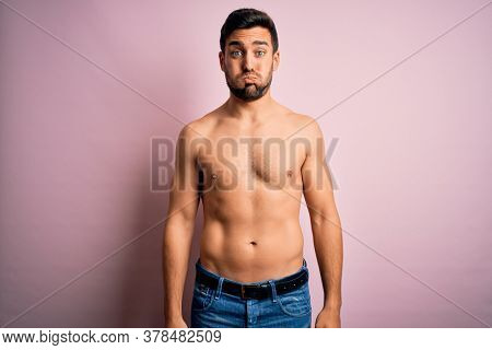 Young handsome strong man with beard shirtless standing over isolated pink background puffing cheeks with funny face. Mouth inflated with air, crazy expression.