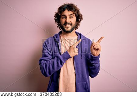 Young handsome sporty man with beard wearing casual sweatshirt over pink background smiling and looking at the camera pointing with two hands and fingers to the side.