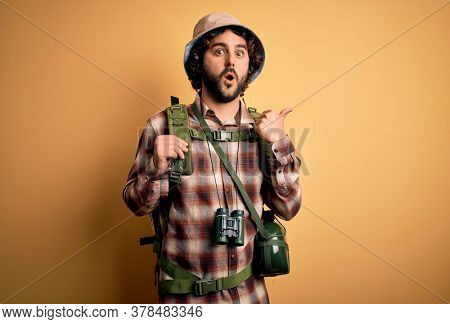 Young hiker man with curly hair and beard hiking wearing backpack and water canteen Surprised pointing with hand finger to the side, open mouth amazed expression.