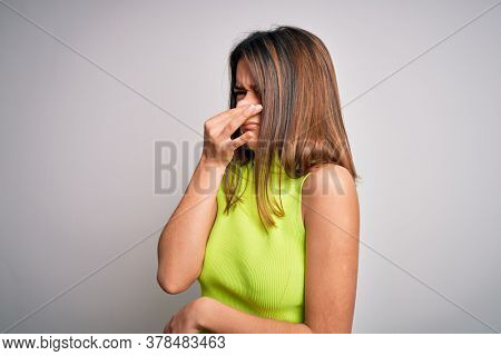 Young beautiful brunette girl wearing casual summer t-shirt over isolated white background smelling something stinky and disgusting, intolerable smell, holding breath with fingers on nose. Bad smell
