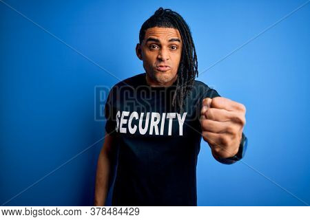 Young african american afro safeguard man with dreadlocks wearing security uniform annoyed and frustrated shouting with anger, crazy and yelling with raised hand, anger concept