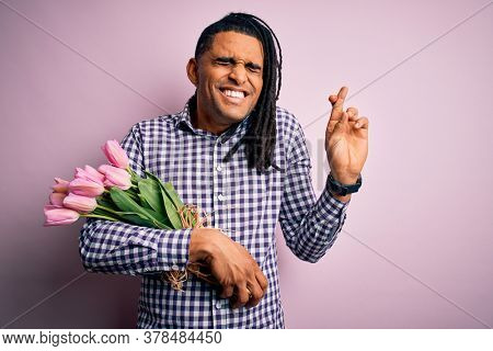 Young african american afro romantic man with dreadlocks holding bouquet of pink tulips gesturing finger crossed smiling with hope and eyes closed. Luck and superstitious concept.