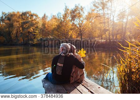 Senior Family Couple Relaxing By Autumn Lake. Man And Woman Enjoying Nature And Hugging Sitting On P