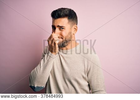 Young handsome man wearing casual sweater standing over isolated pink background smelling something stinky and disgusting, intolerable smell, holding breath with fingers on nose. Bad smell