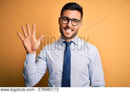 Young handsome businessman wearing tie and glasses standing over yellow background showing and pointing up with fingers number five while smiling confident and happy.
