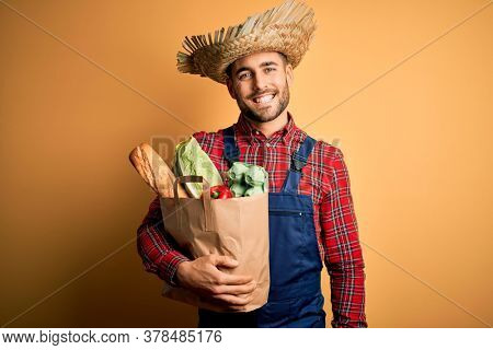 Young rural farmer man holding fresh groceries from marketplace over yellow background with a happy face standing and smiling with a confident smile showing teeth