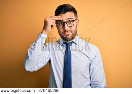 Young handsome businessman wearing tie and glasses standing over yellow background worried and stressed about a problem with hand on forehead, nervous and anxious for crisis