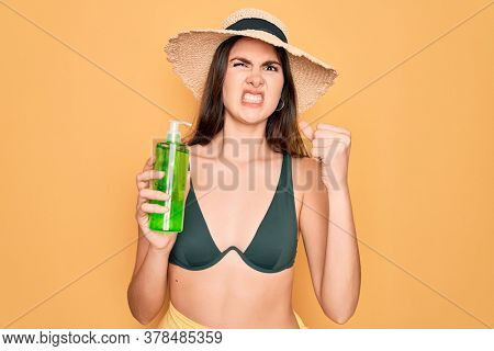 Young beautiful girl wearing swimwear bikini and summer hat holding alove vera sun protection annoyed and frustrated shouting with anger, crazy and yelling with raised hand, anger concept