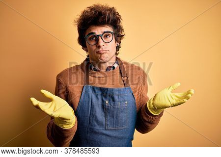 Young handsome cleaner man wearing apron and gloves over isolated yellow background clueless and confused expression with arms and hands raised. Doubt concept.