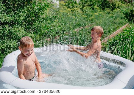 Two Boys Are Playing In The Pool. Childrens Rest In The Backyard. High Quality Photo