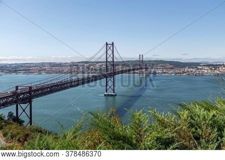 Bridge On April 25 In Lisbon On The Tejo River With Moving Cars.