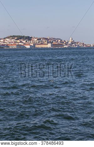 View Of The Historic Waterfront Of Lisbon From The Tejo River. View From The Water On A Summer Day.