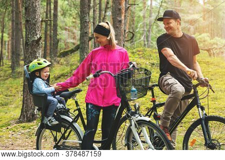Young Happy Family Biking In Forest With Kid In Bike Child Seat. Active Sports Outdoor Recreation