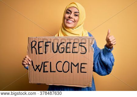 Beautiful arab woman wearing islamic hijab holding banner with refugees welcome message happy with big smile doing ok sign, thumb up with fingers, excellent sign