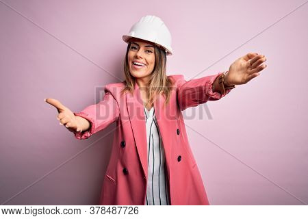 Young beautiful brunette architect woman wearing safety helmet over pink background looking at the camera smiling with open arms for hug. Cheerful expression embracing happiness.