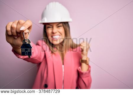 Young beautiful brunette architect woman wearing safety helmet hoding key of house annoyed and frustrated shouting with anger, crazy and yelling with raised hand, anger concept