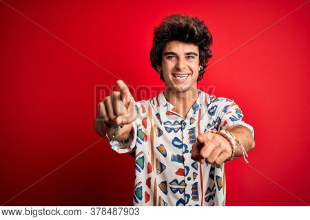 Young handsome man on vacation wearing summer shirt over isolated red background pointing to you and the camera with fingers, smiling positive and cheerful