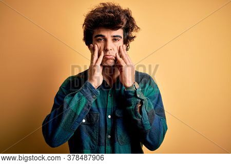 Young handsome man wearing casual shirt standing over isolated yellow background Tired hands covering face, depression and sadness, upset and irritated for problem