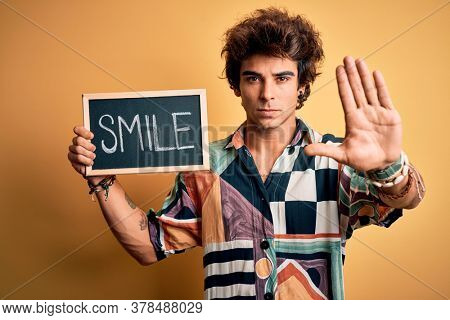 Young handsome man holding blackboard with smile message over isolated yellow background with open hand doing stop sign with serious and confident expression, defense gesture