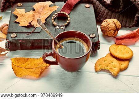 Cup coffee with book in leather binding autumn dry leaf and warm scarf on white wooden board top view.