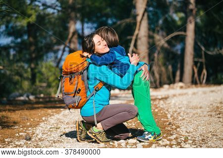 A Child Hugs Mom In The Park. A Woman With A Backpack Walks With Her Son In The Forest. Boy Travels