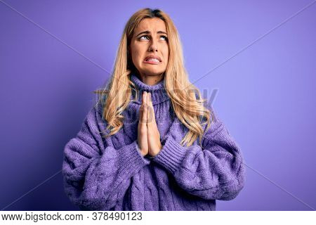 Young beautiful blonde woman wearing casual turtleneck sweater over purple background begging and praying with hands together with hope expression on face very emotional and worried. Begging.
