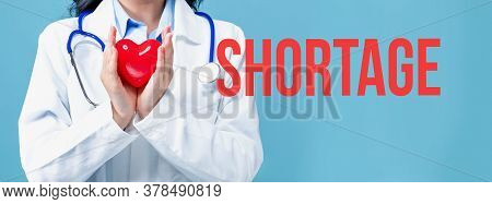Covid-19 Shortage Theme With A Doctor Holding A Heart On A Blue Background