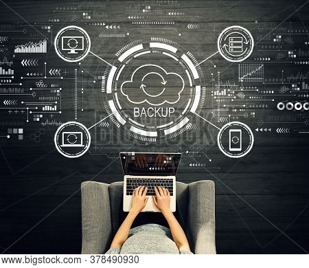 Backup Concept With Person Using A Laptop In A Chair