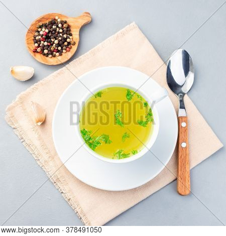 Chicken Broth In A White Cup With Chopped Parsley, Square Format, Top View