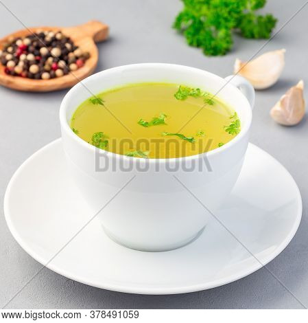 Chicken Broth In A White Cup With Chopped Parsley, Square Format