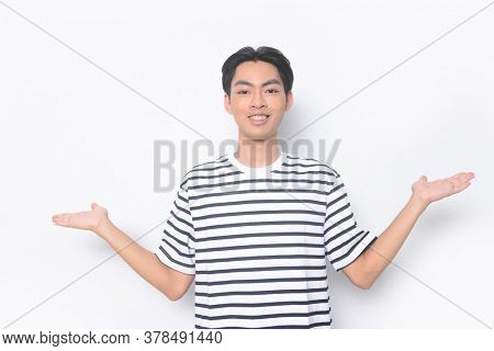 Portrait of smiling young man in striped T- shirt and pointing with palm of hand
