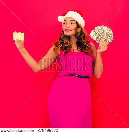 A Beautiful Sexy Woman In A New Year's Hat, Hold In Hands Money And Credit Card Isolated On Red. Cel
