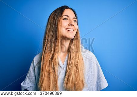 Young beautiful blonde woman with blue eyes wearing striped shirt over blue background looking away to side with smile on face, natural expression. Laughing confident.