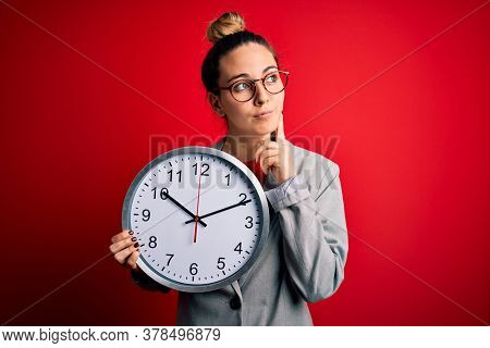 Beautiful blonde woman with blue eyes wearing glasses doing countdown using big clock serious face thinking about question, very confused idea