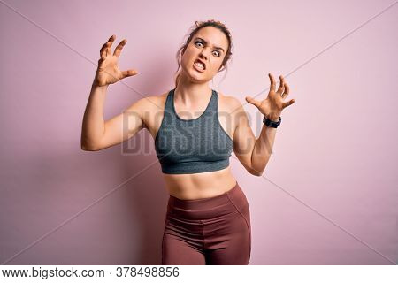 Young beautiful blonde sportswoman doing sport wearing sportswear over pink background Shouting frustrated with rage, hands trying to strangle, yelling mad