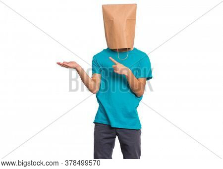Portrait of teen boy with paper bag over head pointing hands away at copyspace, isolated on white background. Child pointing fingers at something.